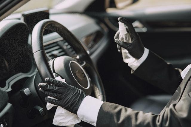 Spraying sanitiser on car dashboard