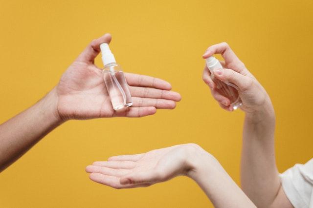 People holding sanitiser bottles