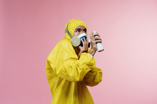 Man in yellow rain coat with spray
